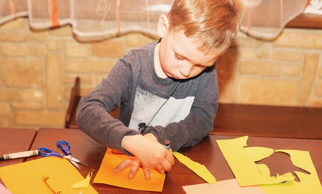 A child tracing his hand to make Thanksgiving Decorations.