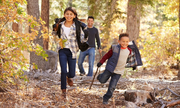 Children running through the woods with their dad while on a nature scavenger hunt.